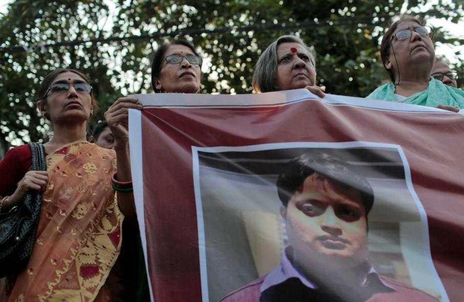 ناشطون يحملون لافتة حملت صورة أنانتا داس في تظاهرة بعد مقتله