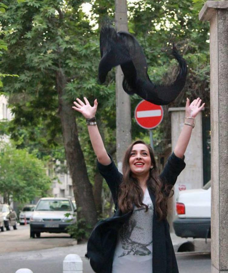 فتاة تلقي بحجابها المفروض عليها في الهواء بأحد الشوارع