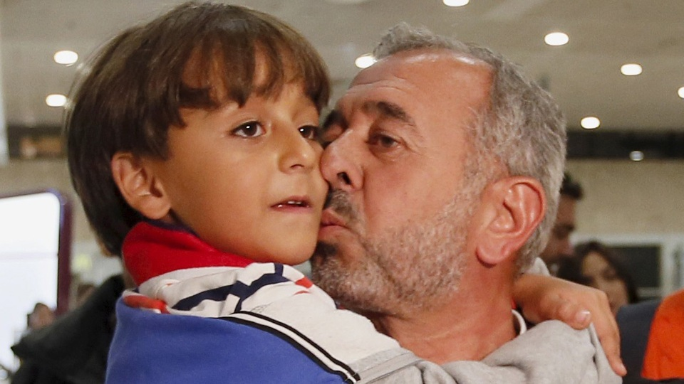 Osama Abdul Mohsen, a Syrian refugee who was filmed being tripped up by a camerawoman as he fled police in Hungary with his young son, kisses his son Zaid upon their arrival at Barcelona's Sants train station