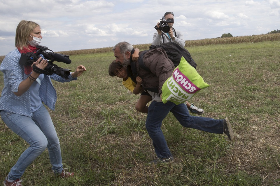 A migrant runs with a child before tripping and falling on TV camerawoman Laszlo as he tries to escape from a collection point in Roszke village, Hungary