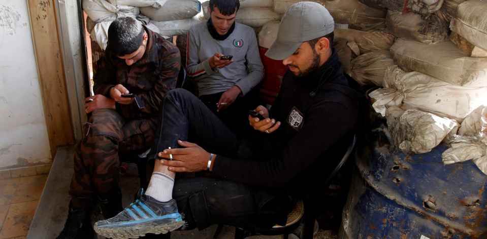 Free Syrian Army fighters use their smartphones behind sandbags in Aleppo