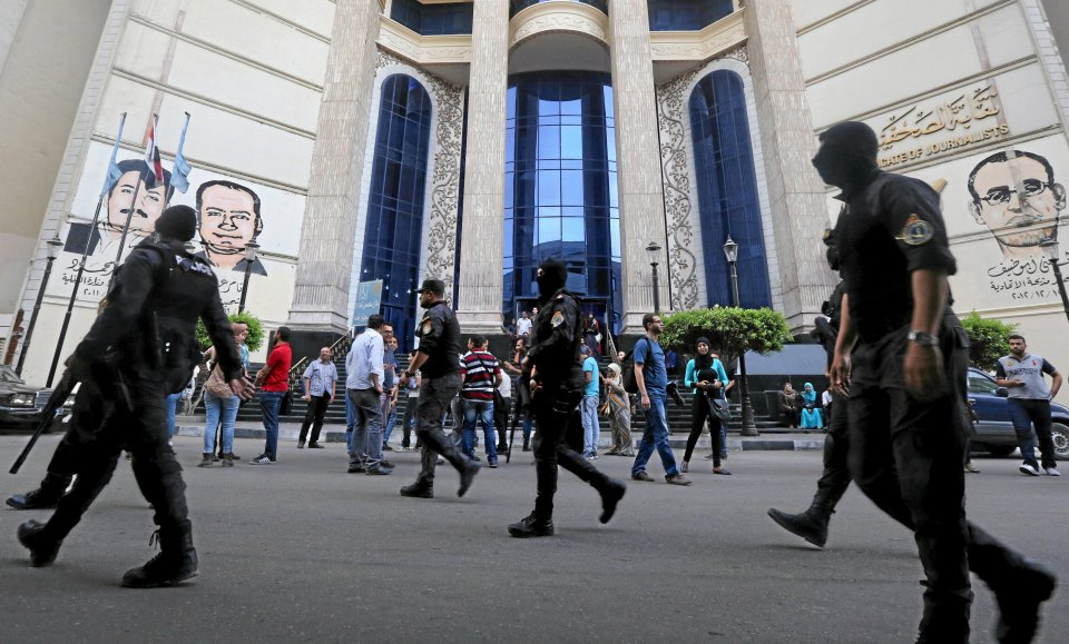 Masked Egyptian security forces walk by a demonstration held by journalists and activists against the detention of journalists, in front of the Press Syndicate in Cairo