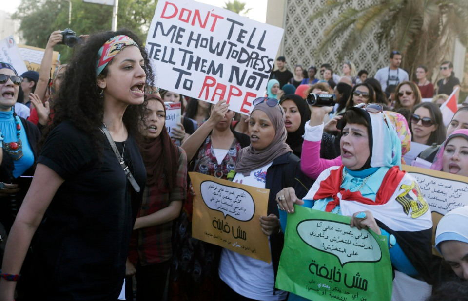Women chant slogans as they gather to protest against sexual harassment in front of the opera house in Cairo